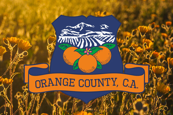 navy blue logo with oranges and mountains and a banner saying orange county, ca