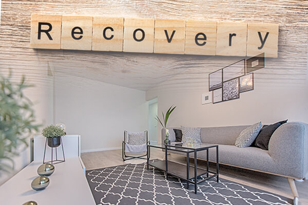 Living room with couch and rug with scrabble letters reading recovery
