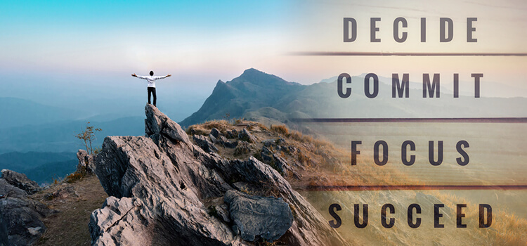 "Man standing on mountain looking accomplished with words ""decide, commit, focus, succeed"" written across"