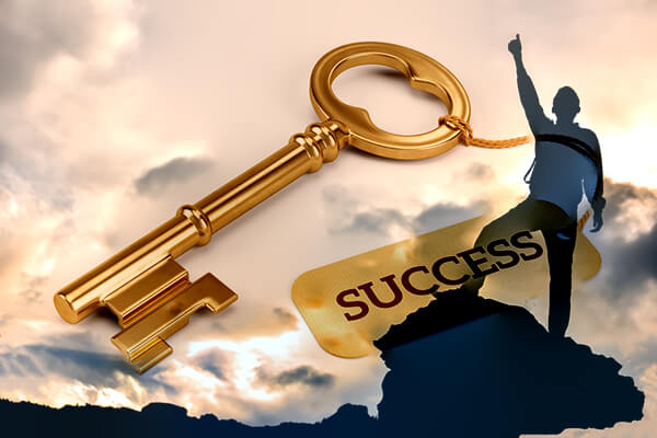 Man standing on mountain wait arm raised white gold key the says success