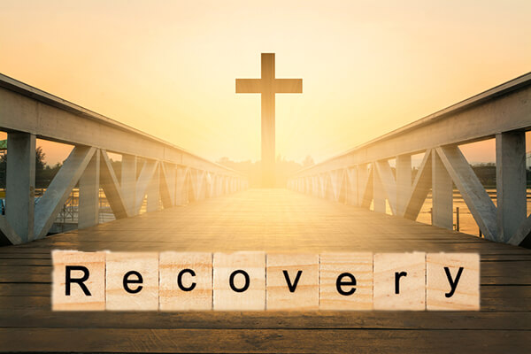 "Bridge over water with cross in the middle with sun shining through and word ""recovery"" written over bridge"