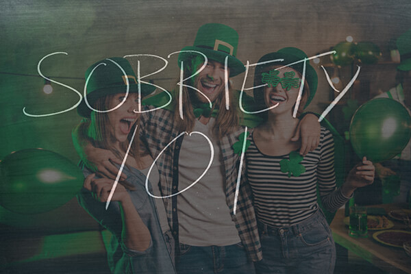 "People gathered for St. Patricks day wearing green and laughing with ""Sobriety 101"" written in thin white letters over photo"