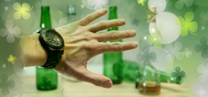 Hand with watch on blocking green beer bottles
